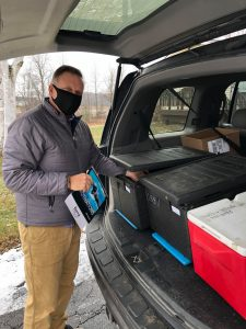 One of our staff members, Jon, loading up and delivering food for Meals on Wheels Vermont. Jon stands at the trunk of his car, filled with containers of food, wearing a mask and looking at the camera.