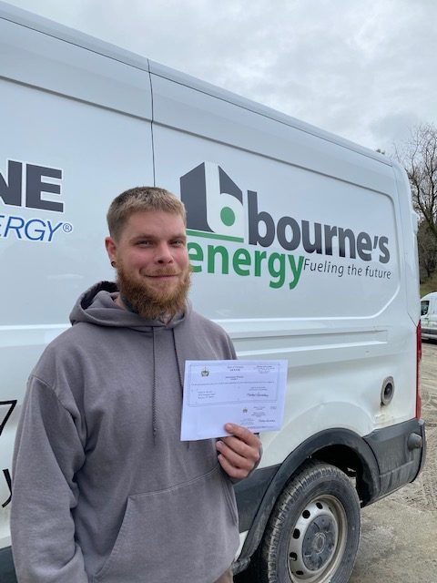 Mark DeVoe stands in front of a Bourne's Energy Service van with his Journeyman's license for plumbing